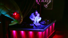 DJ works with players and mixer at his workplace in nightclub Stock Footage