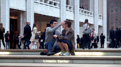 An in tears girl with the guy are sitting on the steps of the Lincoln Center Stock Footage