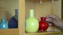 Stock Video Footage of Woman hand put small colorful crockery vases in wall cabinet