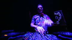 DJ mixes music records with CD-players and mixer during party Stock Footage