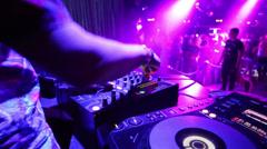 DJ mixes music tracks using CD-players and mixer at nightclub Stock Footage