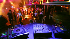 Girls dance at dancefloor in front of table with DJ equipment Stock Footage