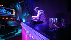 DJ at his workplace in nightclub, camera moves around Stock Footage