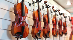 Violins of different sizes hang on exhibition stand Stock Footage