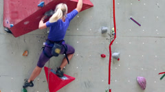 Girl climbs by Rock Wall during rock-climbing competition Stock Footage