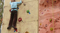 Boy-beginner tries to climb up at rock-climbing wall Stock Footage
