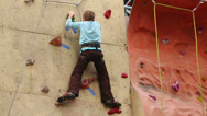 Stock Video Footage of Boy descends down from steep wall at climbing gym hall