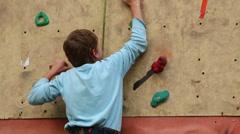 Boy-beginner tries to climb up on vertical rock-climbing wall - stock footage