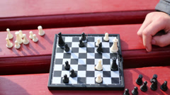 Grandmother move chess piece on chessboard during game in park Stock Footage