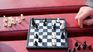 Stock Video Footage of Grandmother move chess piece on chessboard during game in park