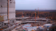 Stock Video Footage of Construction site with buildings, cranes and workers in evening.
