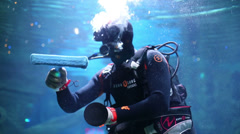 Scuba diver underwater cleans glass wall of aquarium Stock Footage