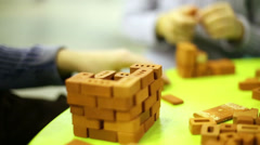 Hands of children who play with toy ceramic bricks on table Stock Footage