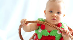 Little girl dressed in knitted strawberry suit sits at basket Stock Footage