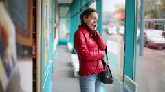 Woman in jacket stands at book shop talking on cell phone. Stock Footage