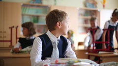Schoolboy sits at his desk in classroom clasping hands. Stock Footage