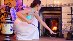 Young woman pokes fire in fireplace at bath complex. Stock Footage