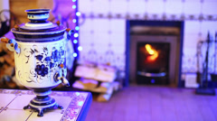 Samovar made in gzhel style on table at room with fireplace. Stock Footage
