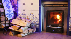 Fireplace with burning flame and stack of birch firewood. Stock Footage
