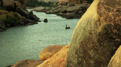 A round boat in a beautiful river, with temple ruins behind. Stock Footage