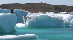 Large icebergs in blue lake Jokulsarlon and moraine dam Stock Footage