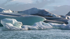 Pan left and zoom out on icebergs and background glacier Stock Footage