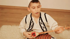 Boy in traditional costume singing and playing string instrument Stock Footage