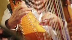 Expert hands playing harp - stock footage