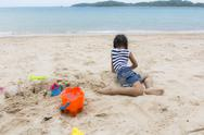 Stock Photo of cute baby girl playing with beach toys