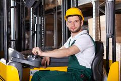 storehouse employee driving on forklift - stock photo
