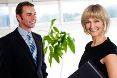 Stock Photo of Handsome boss passing by smiling female colleague