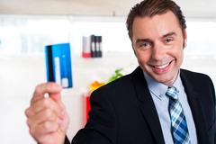 Handsome male executive holding cash card - stock photo