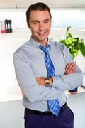 Stock Photo of Young manager in formals standing with arms crossed