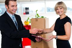 Stock Photo of Boss handing over signed document to his secretary