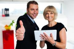 Stock Photo of Secretary with a tablet posing with her successful boss