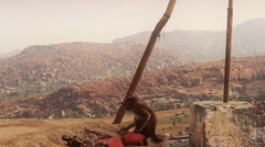 A monkey tries to open a coconut, above rivers, hills and boulders. Stock Footage