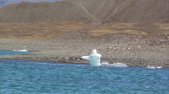 Zoom out from tiny iceberg by the shore to show full lake Stock Footage