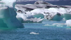 Little piece of ice among large iceberg on turquoise glaciar lake Stock Footage