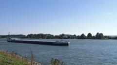 Rhine barge slowly navigates downstream at River Rhine near Tolkamer Stock Footage
