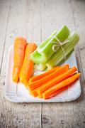 Bundle of fresh green celery stems and carrot Stock Photos
