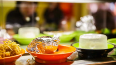 Close up of Chinese food and Sushi on plates moving on a conveyor belt in restau Stock Footage