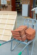 Wheelbarrow with roof tiles to build Stock Photos