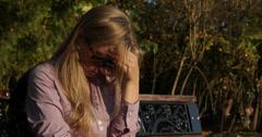 Ultra HD 4K Onneton surullinen nainen istuu puistossa syksyllä päivä avioero surua itkeä tyttö Arkistovideo