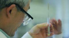 Man examining test tube in labratory - stock footage