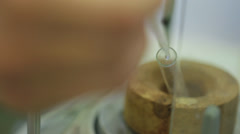 Hand squeezing a dripper into a test tube. - stock footage