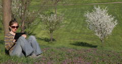 Ultra HD 4K UHD Young girl sitting green grass digital tablet bloom cherry tree Stock Footage