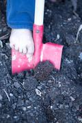 Bare foot of a little child digging with a spade Kuvituskuvat