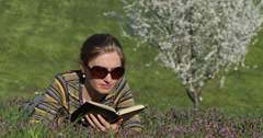 Ultra HD 4K Young student girl study read novel book lying pasture green grass Stock Footage