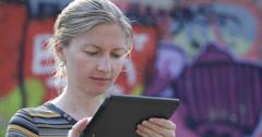 UHD 4K Young woman work digital tablet read document graffiti wall urban scene Stock Footage