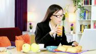 Stock Video Footage of Young asian business woman at home working during breakfast